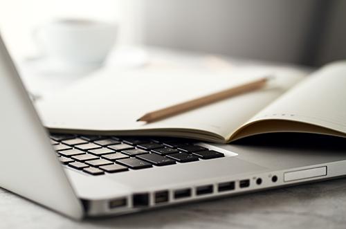 Notizblock und Stift auf Notebook Tastatur